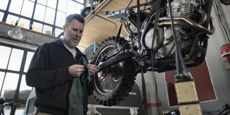 man checking motorcycle tire