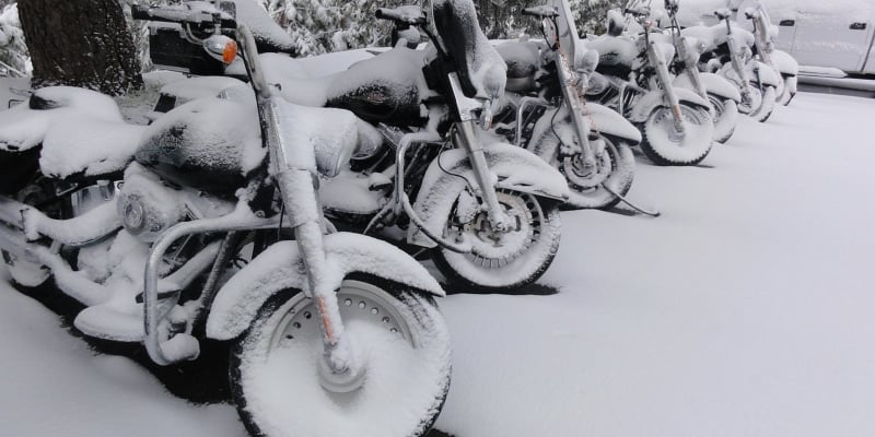motorcycle covered in snow - how long does a motorcycle battery last?