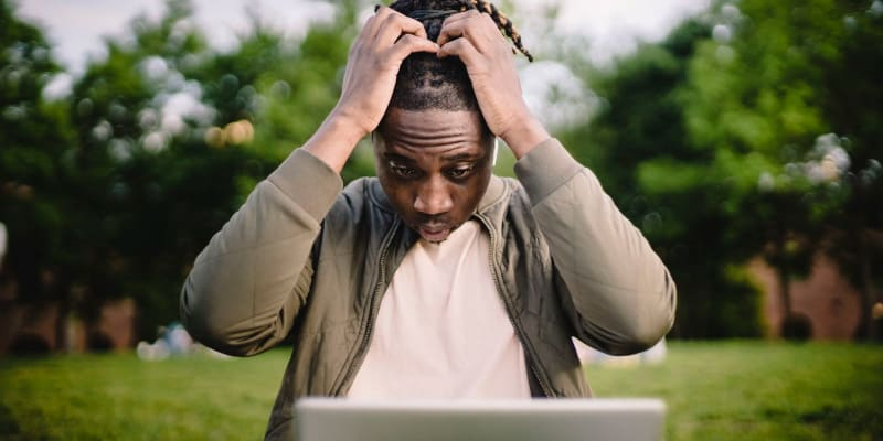 Man looking frustrated while staring at his screen laptop