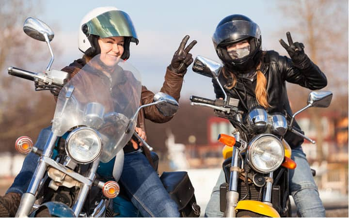 Women wearing leather motorcycle gloves