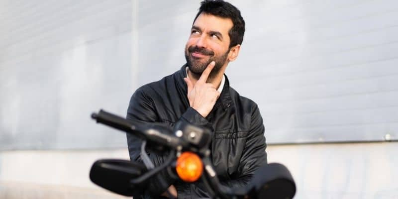 Man thinking while sitting on a motorcycle