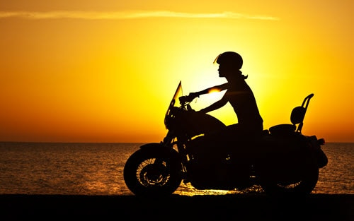 Woman on motorcycle with sun setting over water behind her
