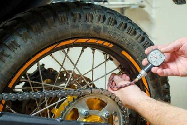 man checking motorcyle tire pressure