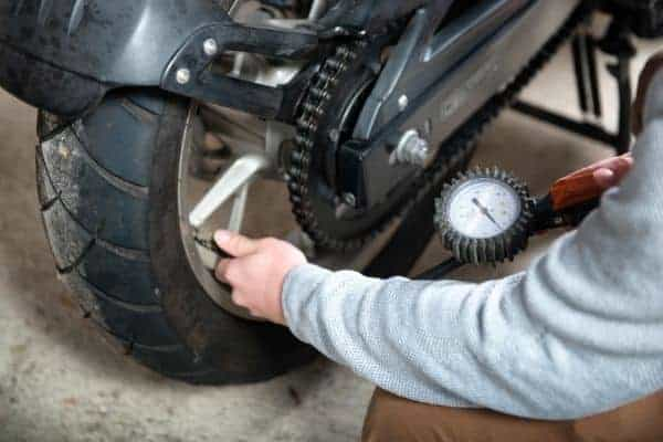 person checking tire pressure on motorcycle