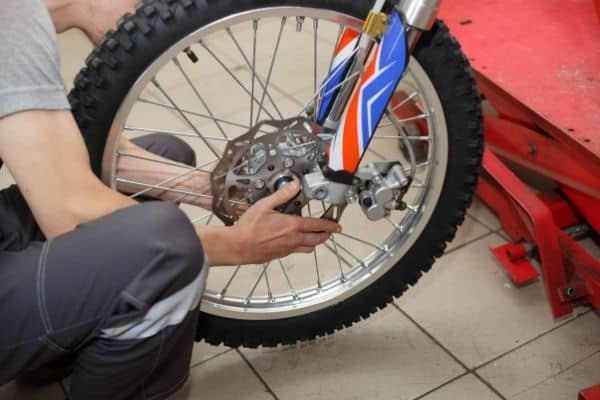 Man fixing motorcycle tire