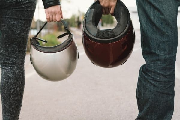 Man and woman holding motorcycle helmet while walking