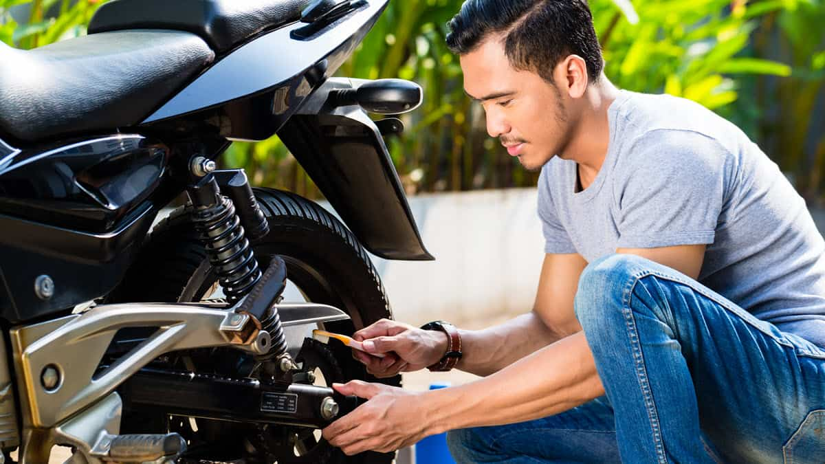 Man performing maintenance on the chain of his motorcycle
