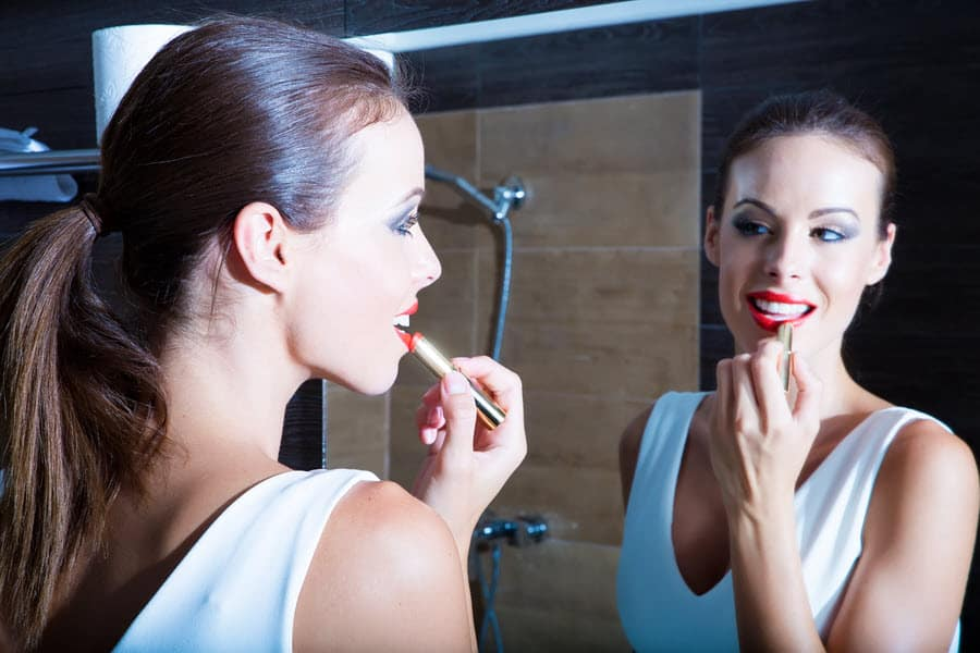 Woman in white dress putting on red lipstick using a mirror