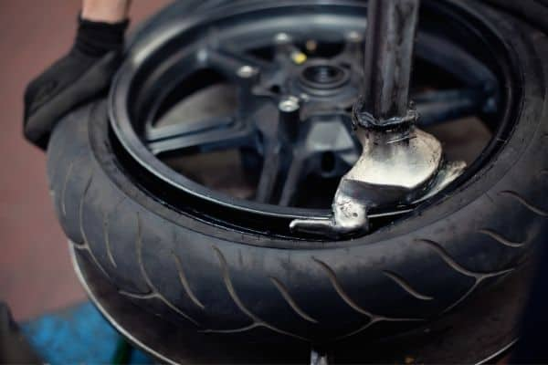 person fixing a michelin motorcycle tire