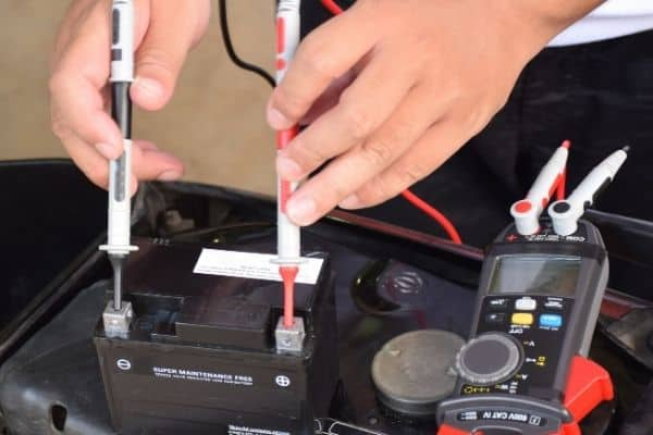 person testing motorcycle battery