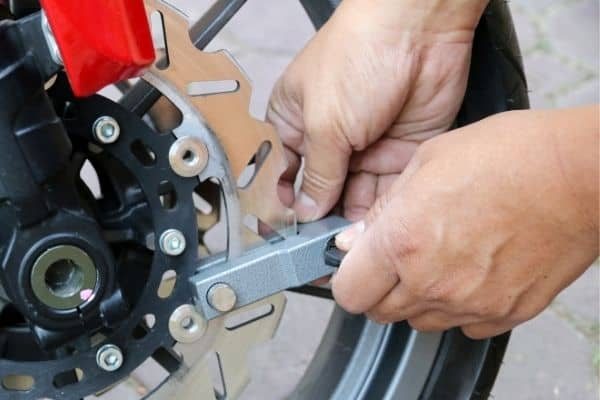 person securing motorcyle with disc lock